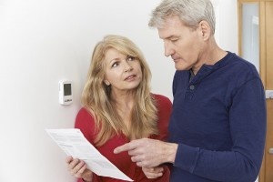 Worried Mature Couple With Bill Turning Down Central Heating