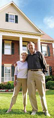 A happy couple in front of their newly renovated country home.