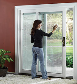A woman opening a sliding glass door.