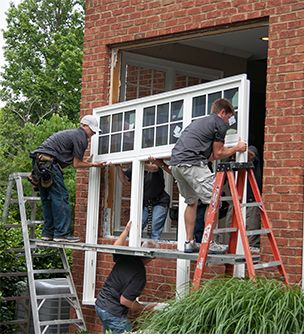 Workmen installing a white three-panel window.