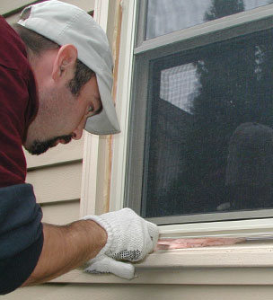 Workman weatherproofing a window.